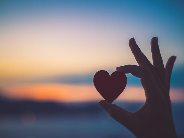 Main de silhouette tenant beau coeur pendant le coucher du soleil.