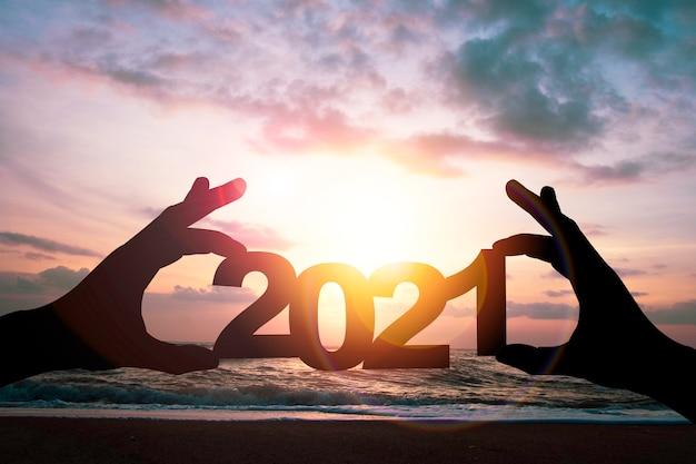 Main de silhouette tenant le numéro 2021 sur paysage marin avec ciel de nuages et lever du soleil. c'est le symbole du début et de la bonne année 2021.