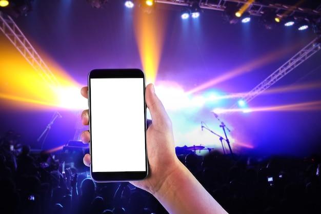 Main avec un smartphone enregistre le festival de concerts de musique en direct.