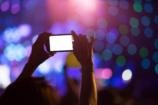 Main avec un smartphone enregistre la fête de luxe avec écran blanc vide
