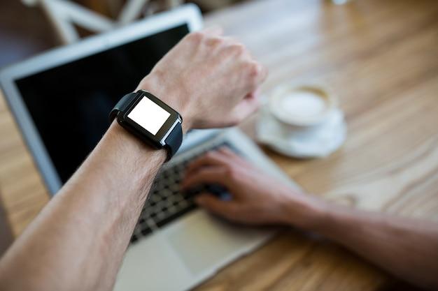 Main smartwatch portant l'aide d'un ordinateur portable dans un café