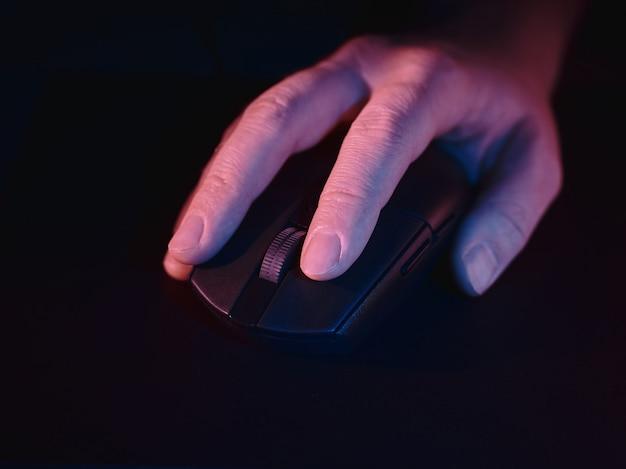 Main et souris d'ordinateur sur une surface noire