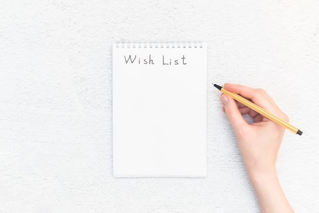 Main avec stylo et carnet de croquis avec espace copie. liste de souhaits.