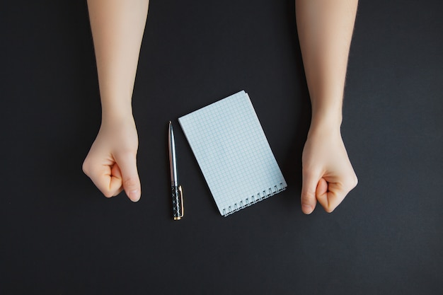 Main avec un stylo et du papier blanc, sur une table sombre