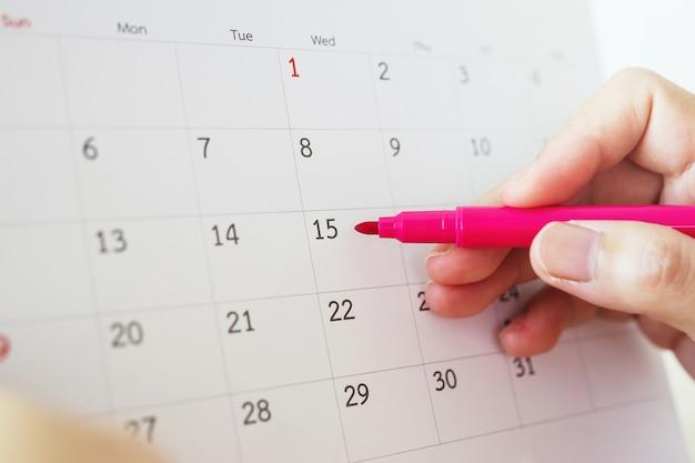 Main avec stylo écrit sur la date du calendrier