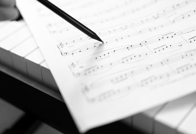 Main avec stylo et feuille de musique - fond musical