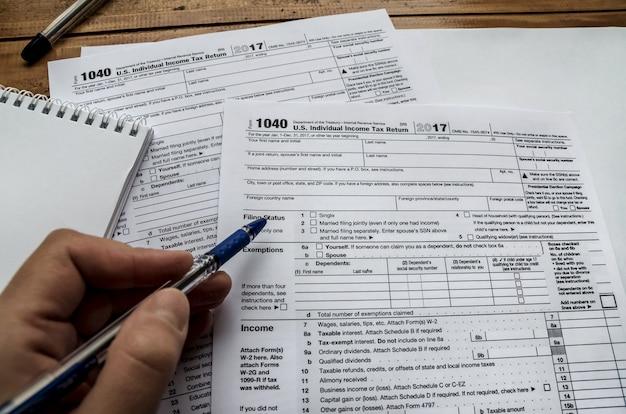 Main avec stylo et formulaires fiscaux 1040