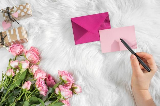 Main avec un stylo près du papier, enveloppe, cadeaux et fleurs fraîches sur une couverture en laine