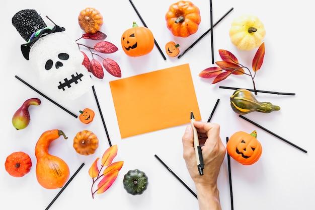 Main avec un stylo près d'un morceau de papier entouré de décorations
