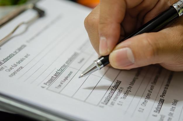 La main avec un stylo rédige des documents d'application sur le bureau.