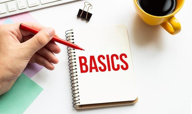 Main avec stylo rouge, tasse à café, bâton, clavier et cahier blanc avec texte basics