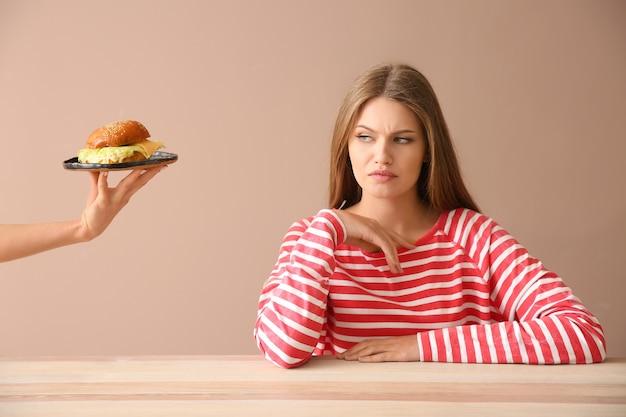 Main suggérant un hamburger à une jeune femme mécontente à table