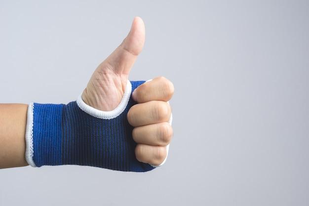 Main avec support de poignet élastique et geste pouce en l'air
