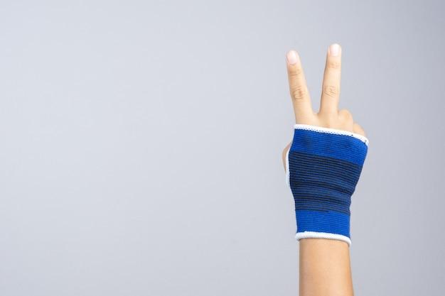 Main avec support de poignet élastique et geste de victoire