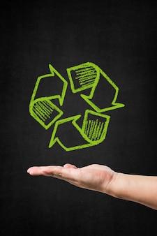 Main avec un symbole de recyclage dessiné sur un tableau noir,