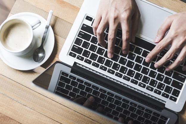 Main en tapant clavier sur une table en bois au café