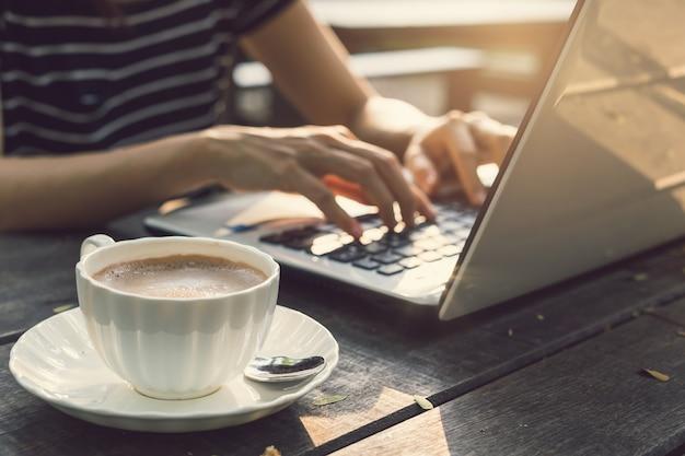 Main, taper sur le clavier ordinateur portable avec une tasse de café