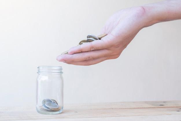 La main avec un tas de pièces et d'économiser des pièces de verre sur une table en bois - concept d'investissement, d'affaires, de finance et bancaire
