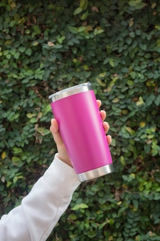 Main sur une tasse en acier inoxydable