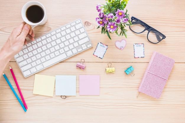 Main avec tasse sur le bureau avec clavier et stationnaire