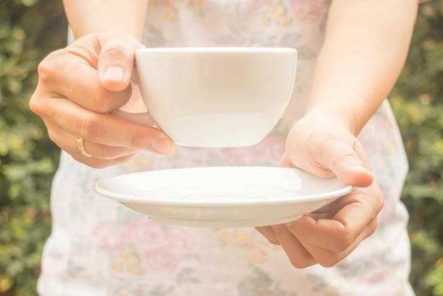 Main sur une tasse de café avec filtre vintage