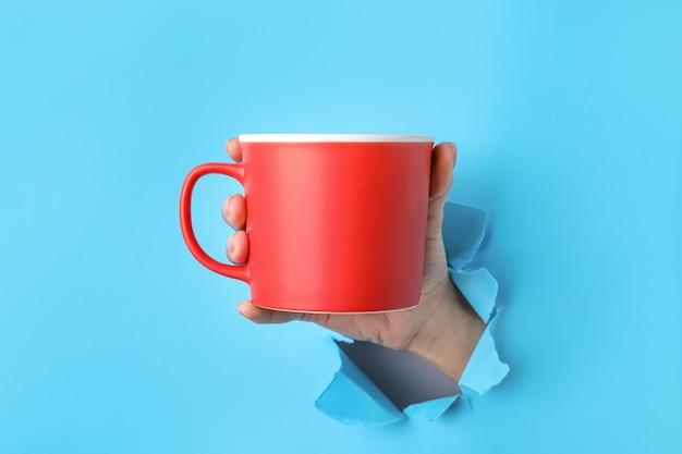 Main avec tasse sur la surface de couleur