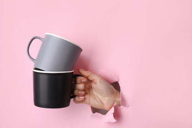 Main avec des tasses sur la surface de couleur