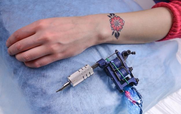 Main avec tatouage et machine à tatouer.