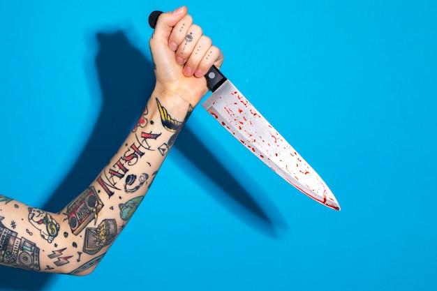 Main avec tatoué tenant un couteau