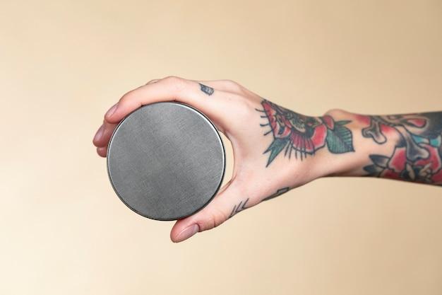 Main tatouée tenant une maquette de pot de crème pour le visage
