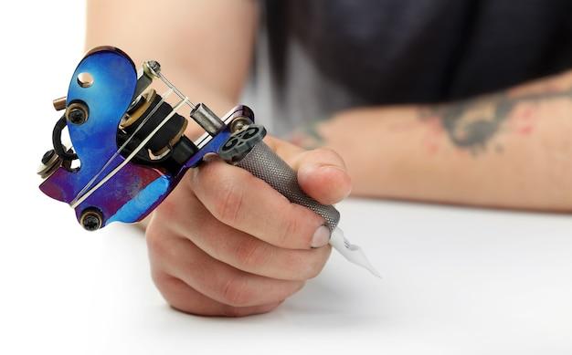 Main de tatoueur avec machine à tatouer au tableau blanc, gros plan