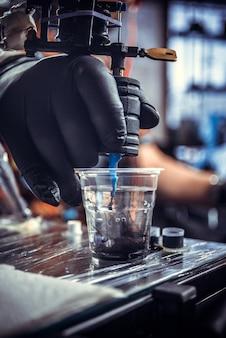 Main de tatoueur professionnel avec un pistolet de tatouage.