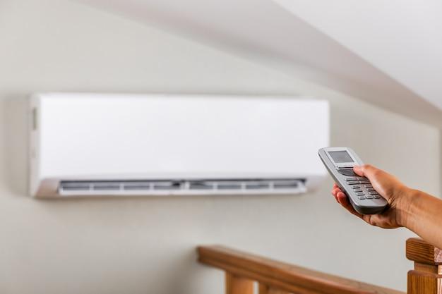 Main avec télécommande dirigée sur le climatiseur sur le mur