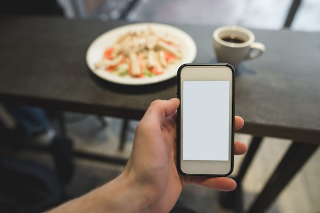 La main avec le téléphone fait une photo de la nourriture dans le restaurant