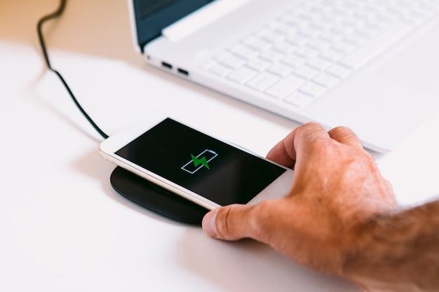 Main avec un téléphone intelligent mobile blanc avec le logo d'une batterie avec un éclair vert sur l'écran, se chargeant sur une base de chargeur sans fil à côté d'un ordinateur portable sur une table de travail blanche