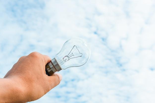 Main tenant l'ampoule et le ciel bleu