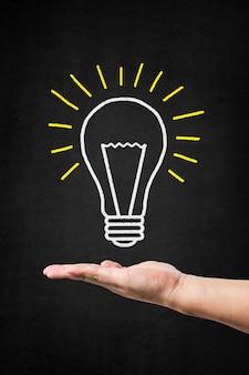 Une main tenant une ampoule dessiné sur un tableau noir,