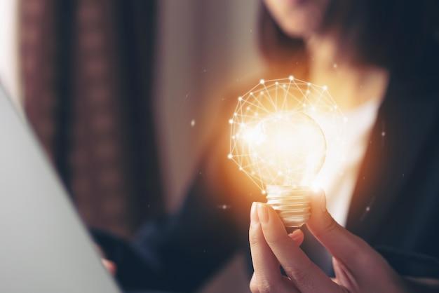 Main tenant une ampoule avec innovation et créativité sont les clés du succès.