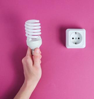Main tenant l'ampoule en spirale sur fond violet. minimalisme