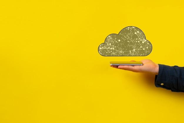 Une main tenant un appareil mobile avec stockage en nuage, base de données en ligne de communication mondiale