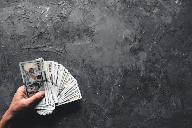 Main tenant de l'argent sur fond sombre. concept d'entreprise, perspective de développement.
