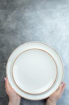 Main tenant des assiettes blanches sur une surface grise avec une surface dégradée à gros grains en détresse