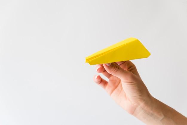 Main tenant l'avion en papier jaune