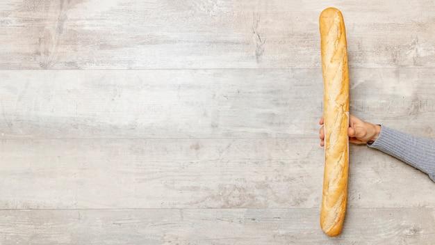 Main tenant une baguette de pain avec espace copie
