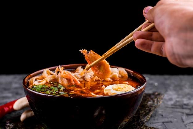 Main tenant des baguettes avec des ramen aux crevettes