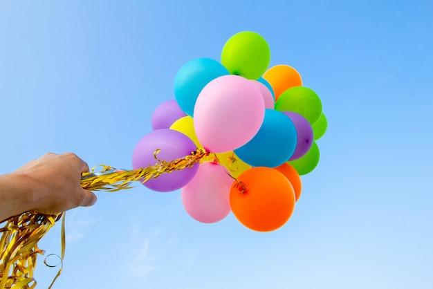 Main tenant des ballons multicolores