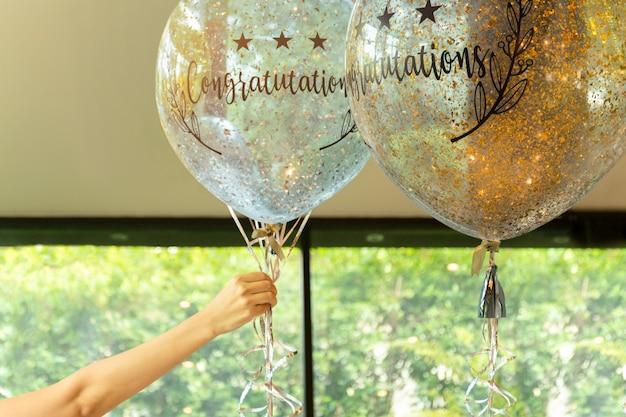 Main tenant des ballons avec le texte de félicitation à ce sujet à la décoration de fête.