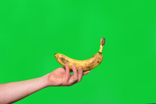 Main tenant une banane sur fond vert