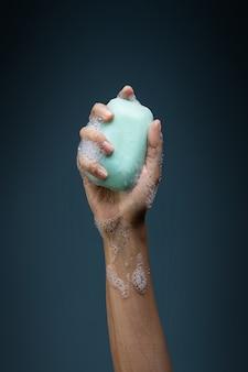 Main tenant une barre de savon et des bulles, victoire contre le concept de coronavirus