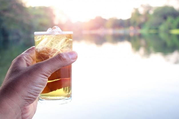 Main tenant la bière pour boire dans la nature.